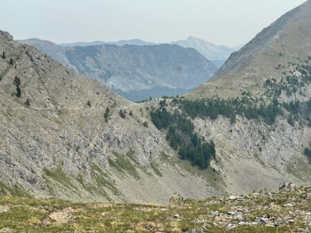 A hiking trail leads through a pass in the mountains, with more mountains visible in the distance.