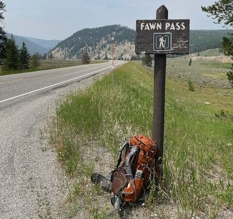 """A backpack rest against a highway sign reading """"Fawn Pass."""""""